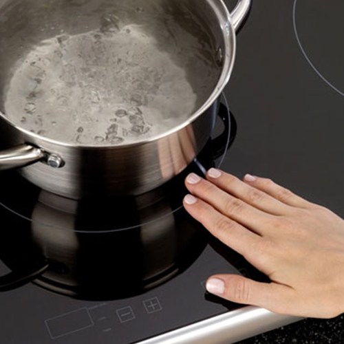 Induction cooktops efficiently heat cookware, while the black ceramic glass cooking surfaces remain cool.